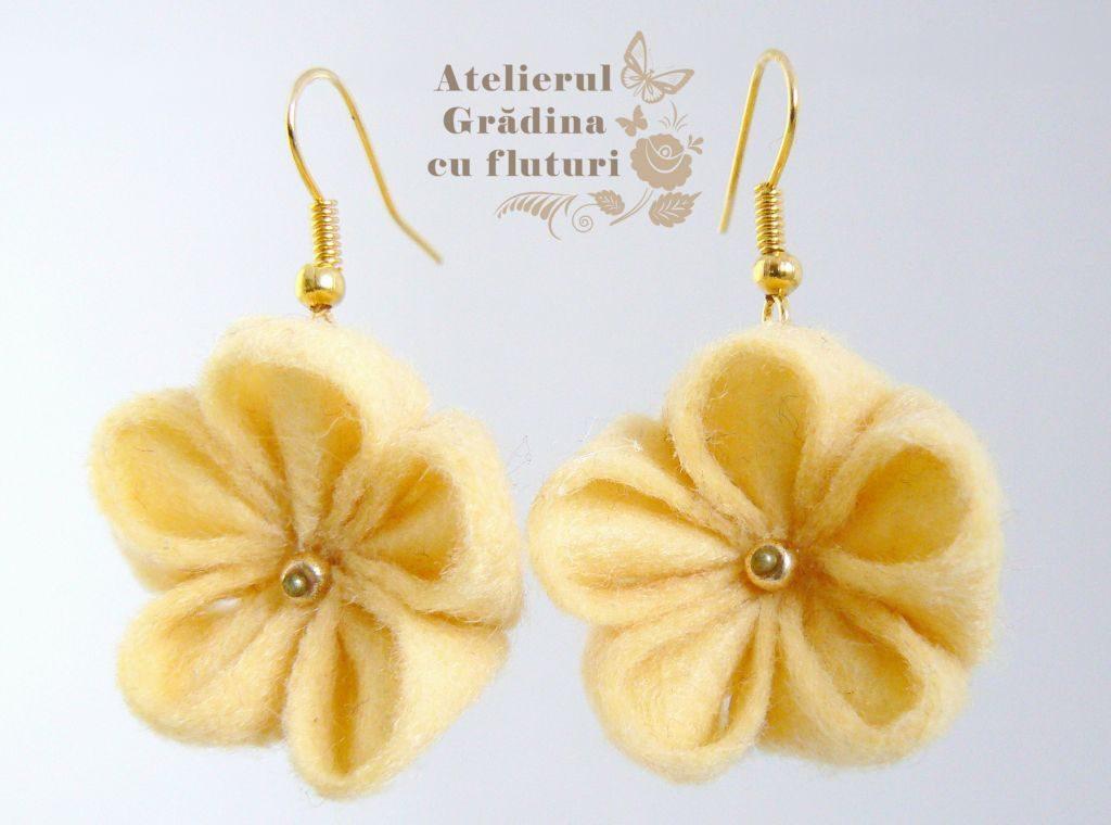 Cercei unicat din pâslă galben pai. Formează un set cu broşa galben pai. Se prind în ureche cu elemente argintii cu cheiţă. Diametru flori: 2.5 cm