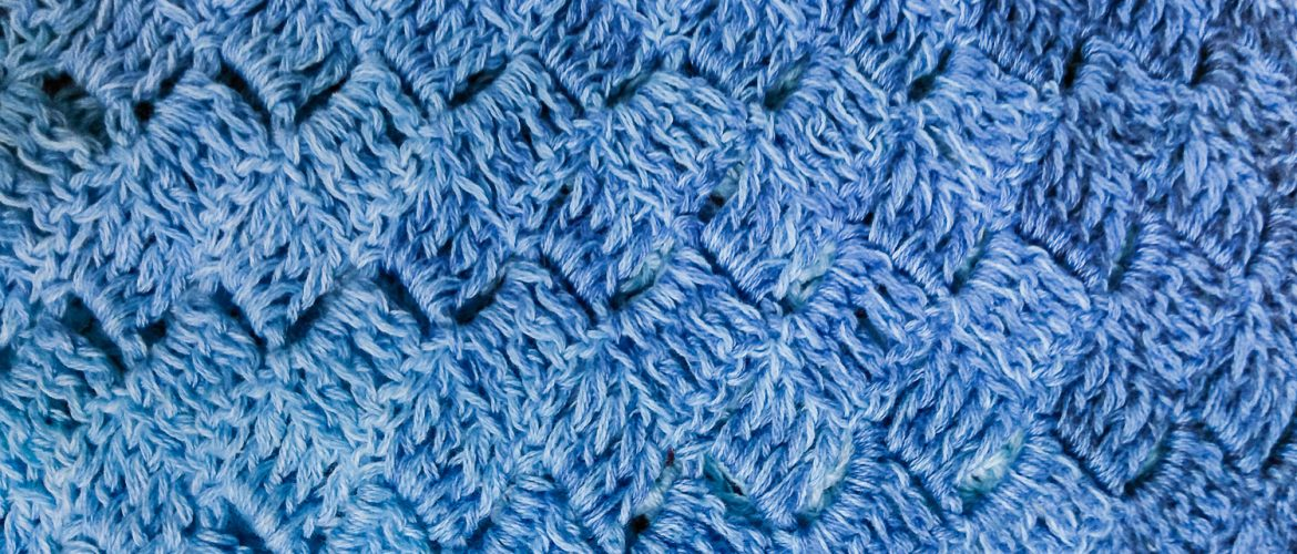Close-up of crocheted shawl in a blue gradient ayrn